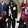 Michael Jackson holds the hands of two children with veils over their heads at Berlin Zoo