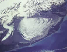 The massive lobe of Malaspina Glacier in Alaska is clearly visible in this photograph taken from a Space Shuttle flight in 1989.  Agassiz Glacier is the smaller glacier to the left.  The Malaspina Glacier is one of the most famous examples of this type of glacier, and is the largest piedmont glacier in the world.  Spilling out of the Seward Ice Field (visible near the top of the photograph), it covers over 5,000 square kilometers as it spreads across the coastal plain. (Photo courtesy of SPACE.com and NASA.)