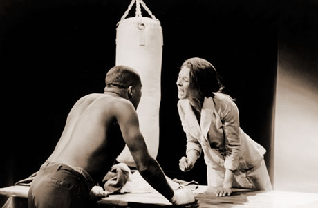 Photograph of an African-American man and a White woman facing each other in a heated exchange.  A table is situated between them and a boxing punching bag can be seen in the background.