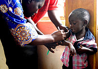 A child's arm circumference is measured to establish one of the indicators that will be transferred by RapidSMS to establish nutritional status. | © UNICEF/2009/Blaschke