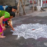 Women in Tamil Nadu drawing the traditional form of Kolam.